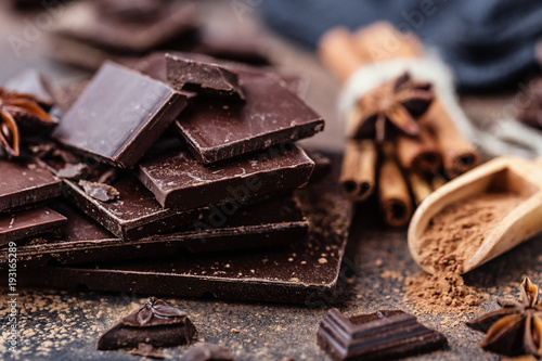 obraz lub plakat Chocolate bar pieces. Background with chocolate. Sweet food photo concept. The chunks of broken chocolate