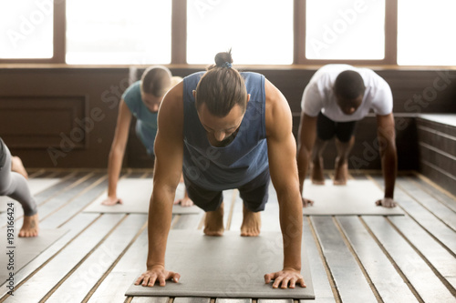 Recess Fitting Yoga school Group of young sporty people practicing yoga lesson standing in Plank pose, doing Push ups or press ups exercise, working out, indoor full length, studio