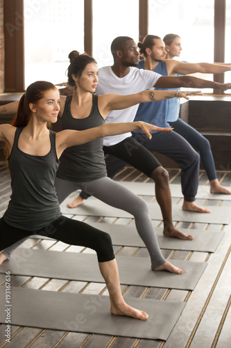 Stampa su Tela Group of young sporty afro american and caucasian people practicing yoga lesson,