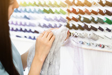 Young Seamstress Selects Threads For Making A Beautiful Fashionable Clothes. Designer Work Place, Small Business Or Startup. Light Textile Industry, Creative Moments Concept Close Up