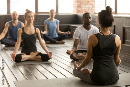 Poster Ecole de Yoga Group of young sporty people practicing yoga lesson with instructor, sitting in Sukhasana exercise, Easy Seat pose, working out, students training in sport club, studio, rear view