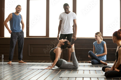 Multiracial People Looking At Sporty Fit Yoga Instructor Performing Raja Bhudjangasana Advanced Exercise Yogi Woman