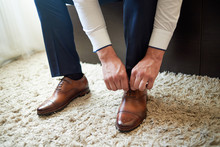 Businessman Tying Shoe Laces Indoors, Close Up. Man Dressing Up With Elegant Leather Shoes. Groom Preparing For Wedding Ceremony At Wedding Day. Man Getting Ready For Work