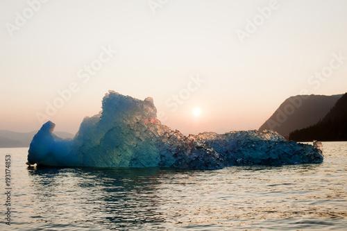 The setting sun illuminated a glacier on the ocean