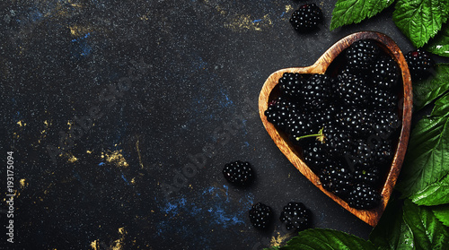 Fresh blackberries with leaves in wooden bowl, black background, top view Fototapeta