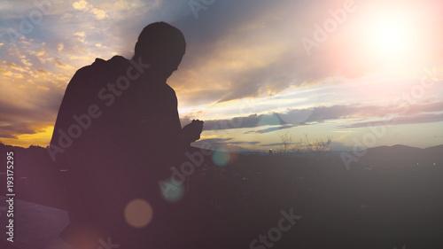 Silhouette of young muslim man praying during sunset