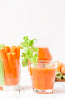 Carrot juice in beautiful glasses, cut carrot and green celery on wood bark bowl on white wooden background. Fresh vegetable drink. Close up photography. Selective focus. Horizontal banner