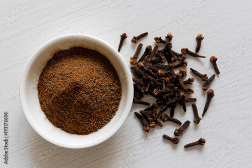 Ground cloves in white ceramic bowl isolated on white wood background from above. Whole cloves.