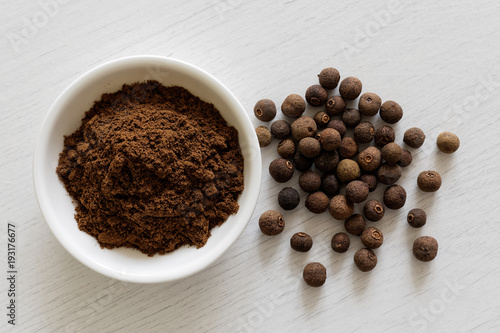 Ground allspice in white ceramic bowl isolated on white wood background from above Wallpaper Mural