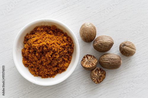 Fototapeta Ground dry mace in white ceramic bowl isolated on white wood background from above. Whole and halved nutmegs. obraz