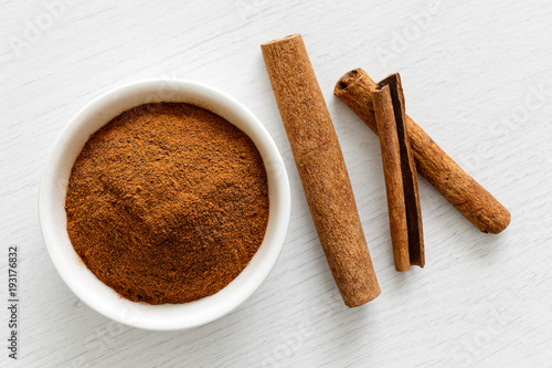 Fototapeta Finely ground cinnamon in white ceramic bowl isolated on white wood background from above. Cinnamon sticks. obraz