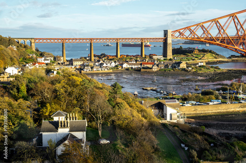 Fototapeta A view from the east footpath of the Forth Road Bridge, looking over North Queensferry towords the old and famous Rail Bridge
