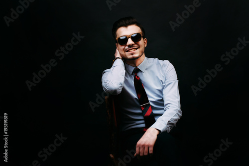 Obraz  Handsome smiling and cheerful young business man in casual sitting on chair and wearing sunglasses and looking at the camera over dark background. - fototapety do salonu