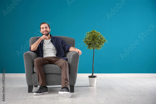 Fotografie, Obraz  Handsome man sitting in comfortable armchair against color wall