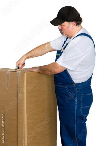 Fotografie, Obraz  Man wearing dungarees opening large cardboard box