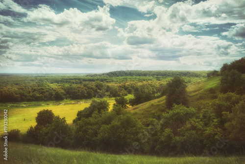 Staande foto Heuvel Fields and meadows in a hilly valley under a cloudy summer sky