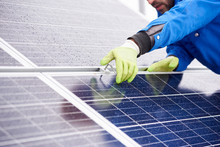 Close-up Of Man With Tools Maintaining Photovoltaic Panels In Snow-covered Weather.