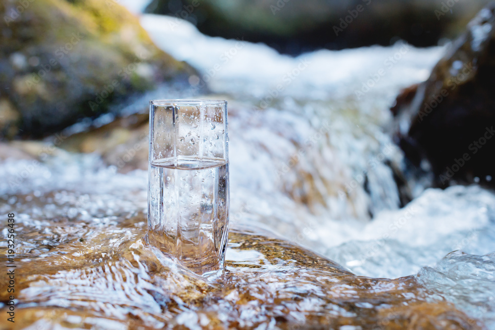 A glass glass with pure mountain drinking water stands on a rock in the course of a mountain river against the backdrop of seething cascades and waterfalls of a mountain river. The concept of pure