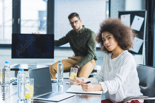 Fototapety, obrazy: multicultural businessman and businesswoman looking at camera in office