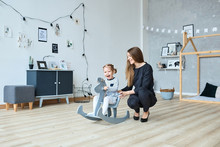 A Happy Little Girl And Her Mom Are Playing Indoors. A Child Riding A Toy Rocking Horse. Toys For Preschool Age. A Happy Family. Mom And Daughter Together.