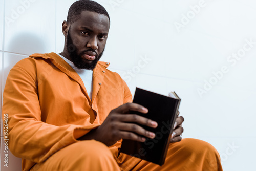 Photo african american prisoner holding book and looking at camera