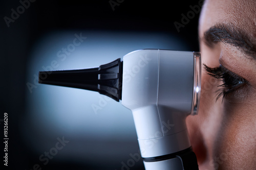 Female doctor using otoscope, side view, close up Canvas Print