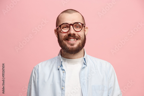 The happy business man standing and smiling against pastel background.