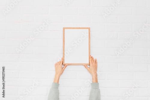 Fotografía  young woman hanging blank posteron wall