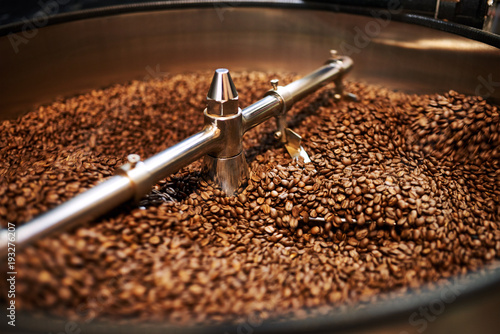 Cuadros en Lienzo Stainless steel arms mixing freshly roasted coffee beans in large stainless steel cooling drum where the beans are cooled down before packaging or storing them