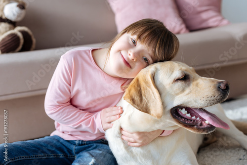 Fotografie, Obraz  Child with down syndrome cuddling with dog