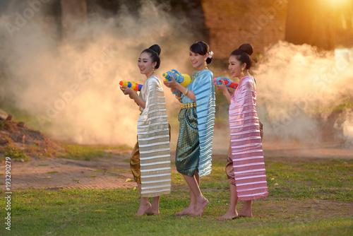 Photo Thai girls and laos girls splashing water during festival Songkran festival