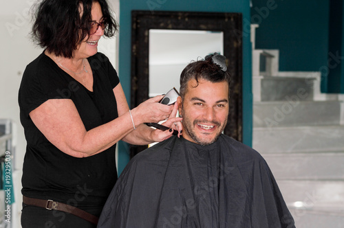 Spoed Foto op Canvas Kapsalon Female barber working with hair clipper, shaving young man's head