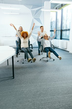 Office. People Having Fun And Racing On Chairs.