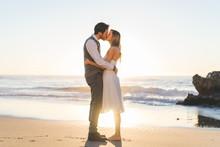Tender Kissing Bridal Couple In Sunlight