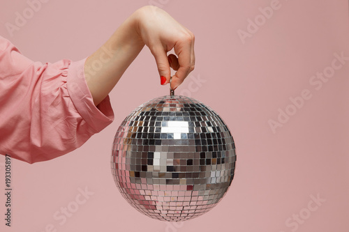 Fotografia Mirror disco ball girl holding her hand on pink background