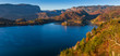 Bled, Slovenia - Panoramic skyline view of Lake Bled with warm autumn foliage and the famous Pilgrimage Church of the Assumption of Maria and the Alps at background