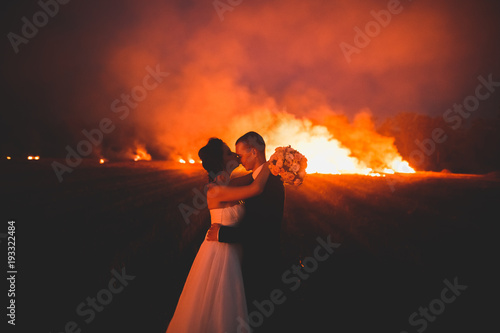 Photo sur Aluminium Orange eclat Amazing wedding couple near the fire at night