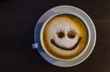White cup on a saucer with coffee. Coffee with foam and smiley patterns.