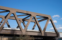 Truss Railway Bridge With Riveted Construction Against Blue Sky