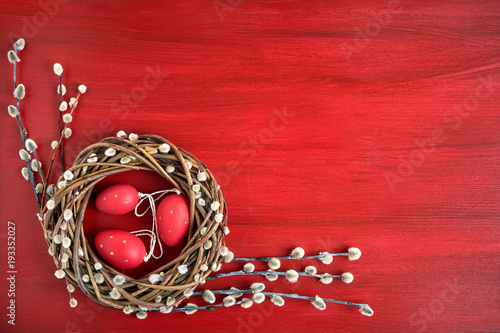 Red Easter background. Easter willow wreath with red  Easter eggs on red background. Top view, copy space. Greeting card