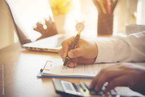 Fotomural  Closeup of new homeowner signing a contract of house sale or mortgage papers with a wooden toy house on the document