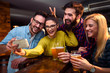 Group of young friends in bar drinking beer having fun