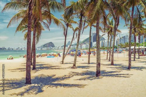 Sunny day with palm trees on Copacabana Beach. Summer time. Rio de Janeiro, Brazil