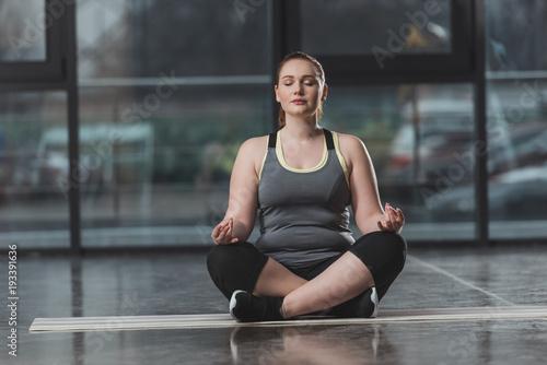 Obraz na plátne Curvy girl during meditation in gym