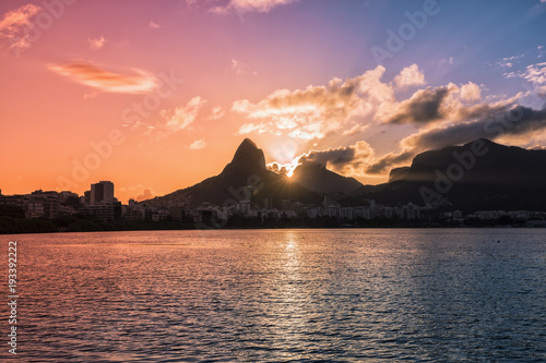 Sunset over mountains in Rio de Janeiro with water reflection and light leak, Brazil