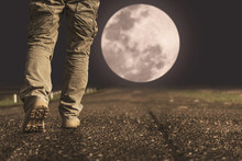 A Man And Sneaker Shoes Walking Under Full Moon At Night
