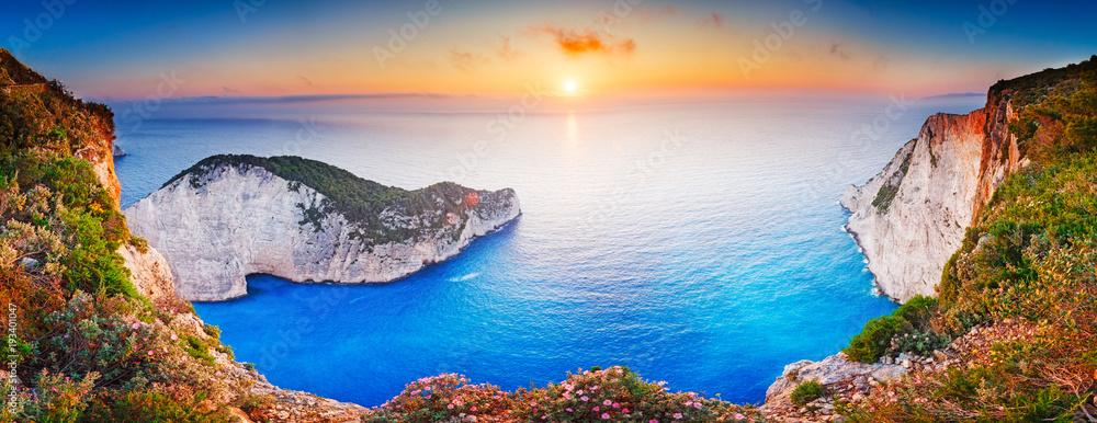 Fototapeta Greece. Epic sunset scenery of Zate island, full name is Zakynthos - popular summer resort and European travel destination in Greece. Picturesque Navagio beach panorama with shipwreck landmark.