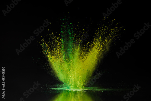 green and yellow holi powder explosion on black, traditional Indian festival of Canvas