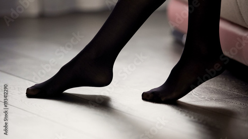 Obraz Elegant female legs in black tights on the floor, style and fashion, clothing - fototapety do salonu