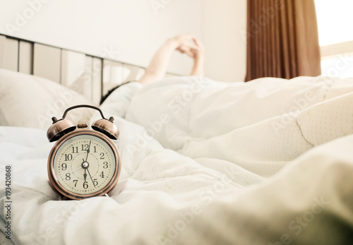 Man stretched in bed after the alarm clock in the sunlight morning Poster